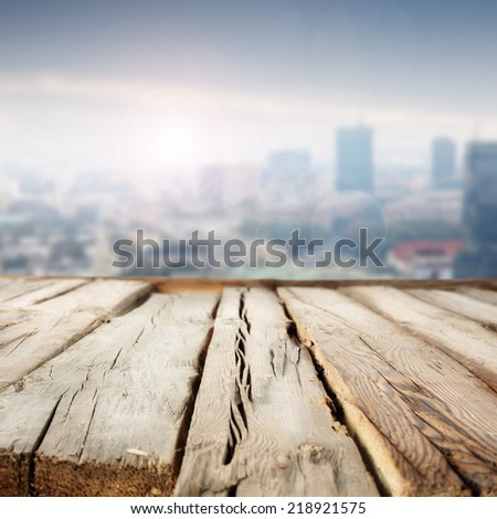worn wooden desk and city place of blue sky