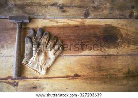 Worn work gloves with hammer on wooden work table - stock photo