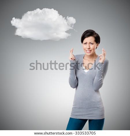 Worrid woman shows crossed fingers to cloud, isolated on grey - stock photo
