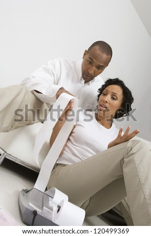 Worried African American couple looking at expense receipt - stock photo