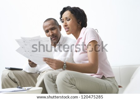 Worried African American couple looking at their bills - stock photo