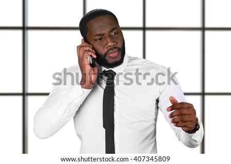 Worried afro guy with cellphone. Chief's phonecall on white background. Don't lose your hope. Big serious problems. - stock photo