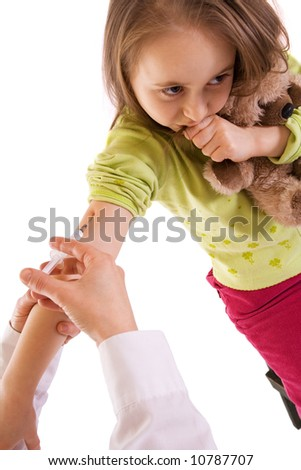 Worried and afraid little girl receiving an injection - studio shot - isolated