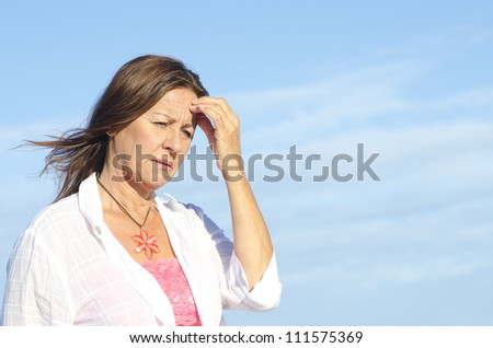 Worried and concerned looking senior woman outdoor, isolated with blue sky as background and copy space. - stock photo