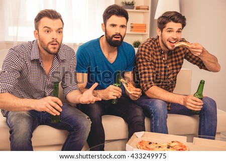 worried and concerned   men sitting on sofa and watching sport tv with beer and pizza - stock photo