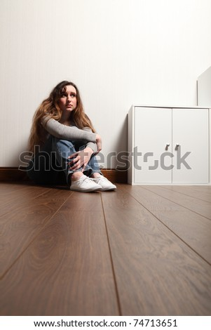 Worried and frightened looking teenage girl sitting alone on the floor at home. - stock photo