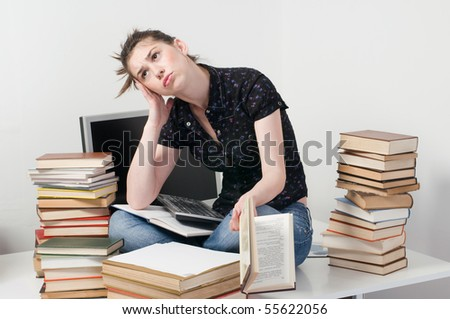 Worried and nervous student girl sitting on desk between her books - stock photo