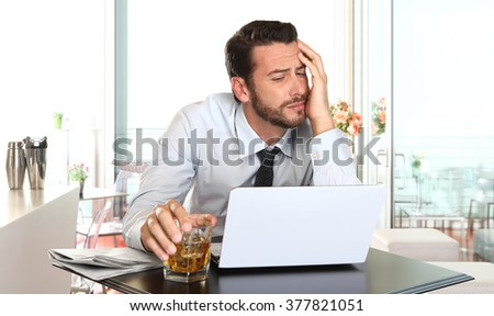 worried and tired businessman in crisis working on computer laptop at bar table in stress under pressure facing work problems - stock photo