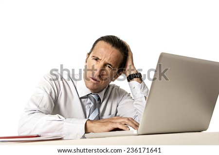 worried and tired senior businessman in crisis working on computer laptop at office desk in stress under pressure facing work problems isolated on white background - stock photo