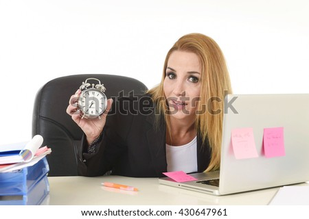 worried attractive blond businesswoman holding alarm clock sitting at office desk working with computer laptop in long hours of work and business stress concept isolated on white background - stock photo