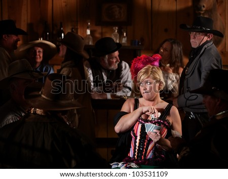 Worried bar maid pulls playing cards from bra in tavern - stock photo