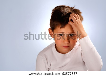 worried boy scratching his head - stock photo