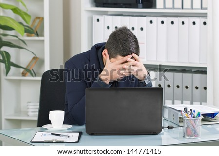 worried business man sitting in a chair at office - stock photo