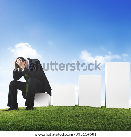 Worried Business Man Sitting on a Bar Graph - stock photo