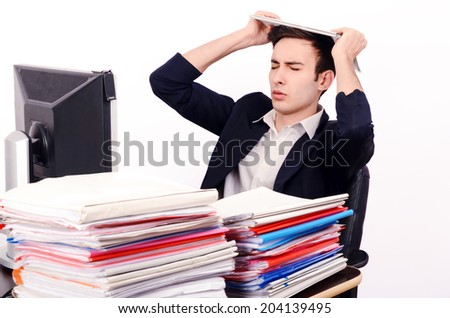 Worried business man with a lot of work. Unhappy worker with a big pile of files to work on.