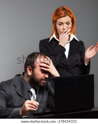 Worried business team anxiously looking at laptop  - stock photo