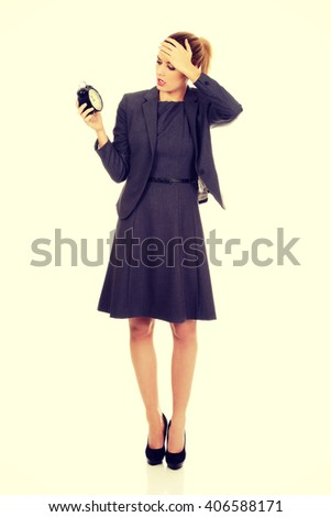 Worried business woman holding alarm clock - stock photo