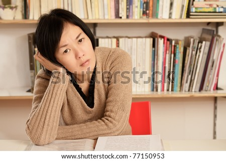 Worried business woman sitting and put hand on head looking at you, half length closeup portrait indoor.