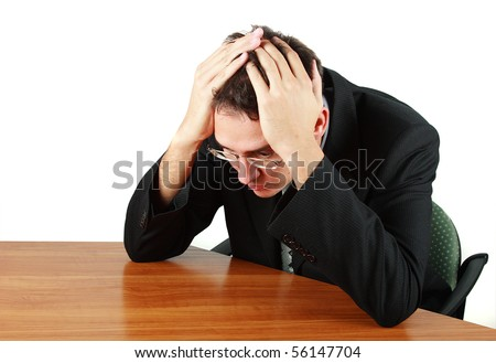 Worried businessman at the table against white background - stock photo