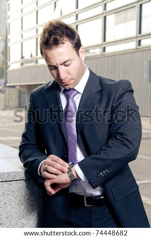 Worried businessman checking time - stock photo