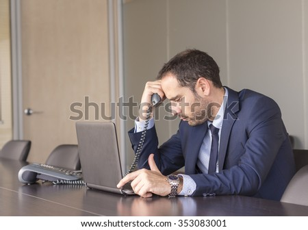 Worried businessman holding his head in his office - stock photo