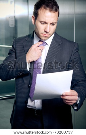 Worried businessman holding important document - stock photo