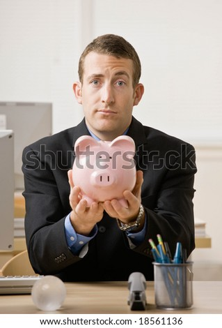 Worried businessman holding piggy bank hoping for future savings
