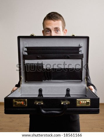 Worried businessman opening empty briefcase - stock photo
