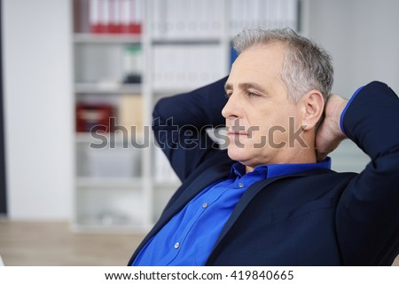 Worried businessman pondering on a problem sitting with his hands clasped behind his head staring ahead with a solemn contemplative expression