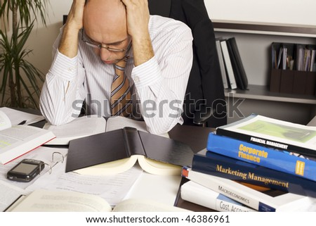 Worried businessman sitting at desk in office being overloaded with loads of work - stock photo