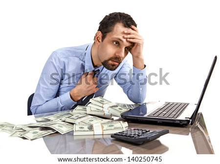 Worried businessman sitting at office desk being overloaded with work and accounting money  - stock photo