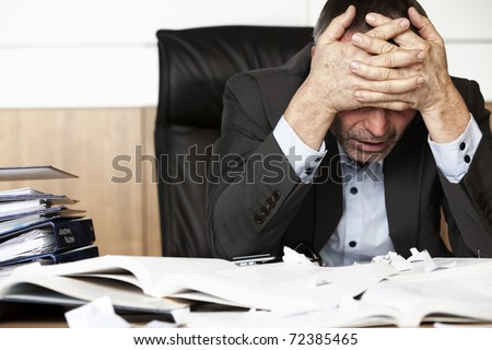 Worried businessman sitting at office desk full with books and papers being overloaded with work. - stock photo