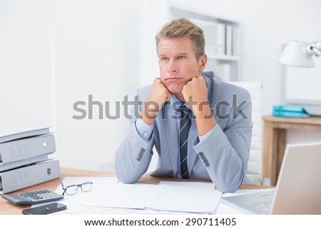 Worried businessman sitting at work in his office - stock photo