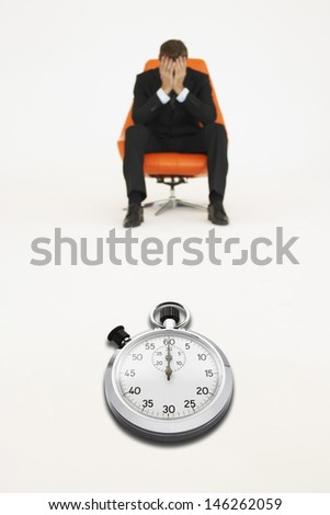 Worried businessman sitting on chair with stopwatch representing loss of time - stock photo