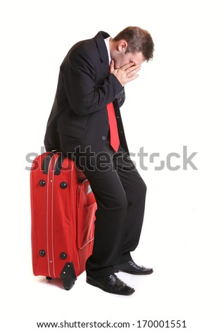 Worried  businessman sitting on red luggage isolated on white - stock photo