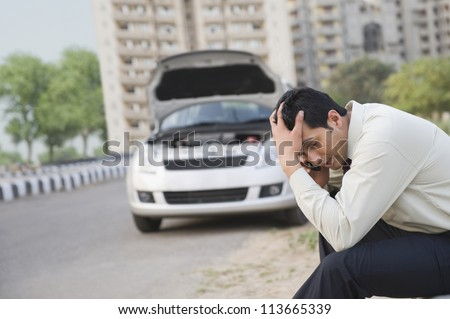 Worried businessman talking on a mobile phone after his vehicle breakdown - stock photo