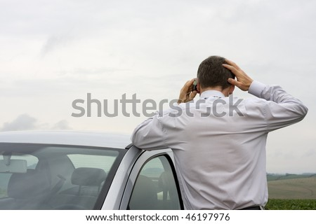 Worried businessman talking on cell phone beside his car - stock photo