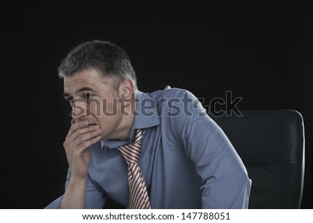 Worried businessman with hand on mouth against black background - stock photo