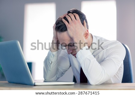 Worried businessman with head in hands in the office - stock photo