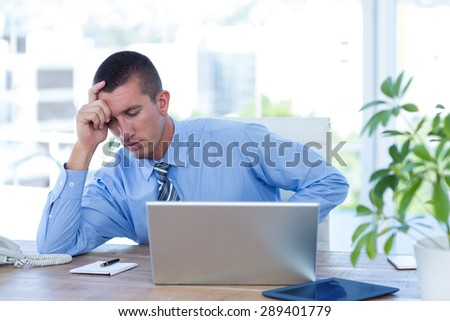 Worried businessman with head in one hand in his office - stock photo