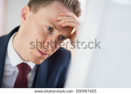 Worried businessman working at his desk in his office - stock photo