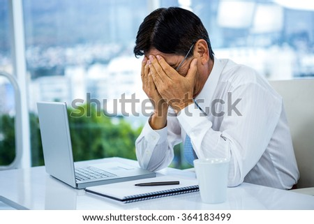 Worried businessman working at his desk in office - stock photo