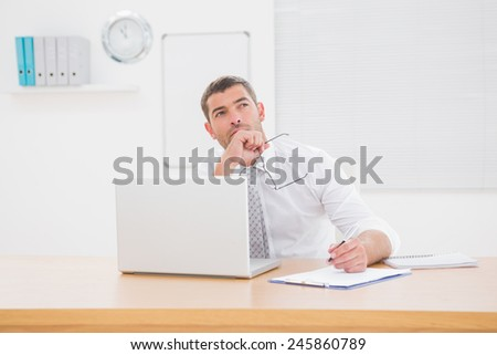 Worried businessman writing on is notepad in his office - stock photo