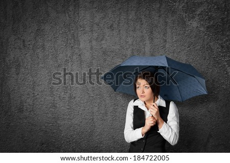 Worried businesswoman hide and protect herself under umbrella.