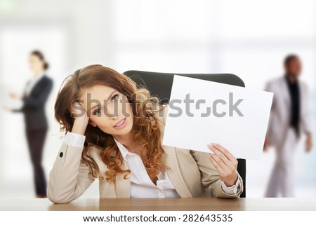 Worried businesswoman holding a blank paper sheet. - stock photo