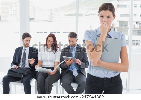 Worried businesswoman looking at camera holding a folder - stock photo
