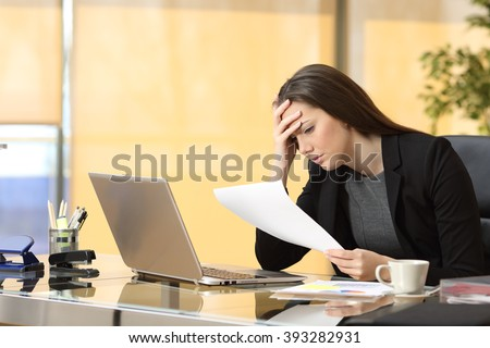 Worried businesswoman reading a notification while is working sitting in a desk at office - stock photo