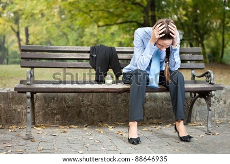 worried caucasian businesswoman sitting on bench in park - stock photo