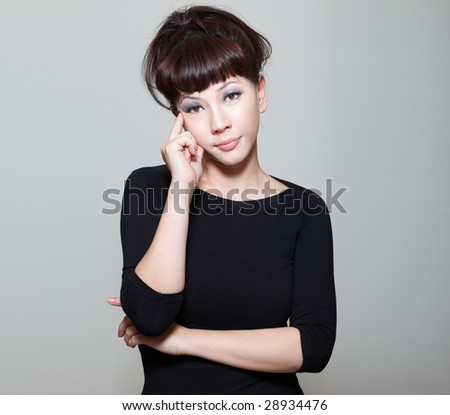 Worried chinese young woman with a contemplative expression looking into camera - stock photo