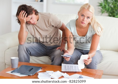 Worried couple calculating their expenses in the living room - stock photo
